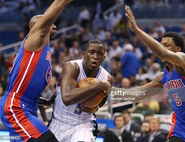 The Orlando Magic's Victor Oladipo drives between the Detroit Pistons' Anthony Tolliver left and Kentavious CaldwellPope right at the Amway Center in...