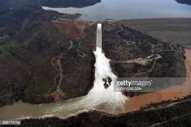 TOPSHOT The Oroville Dam spillway releases 100000 cubic feet of water per second down the main spillway in Oroville California on February 13 2017...