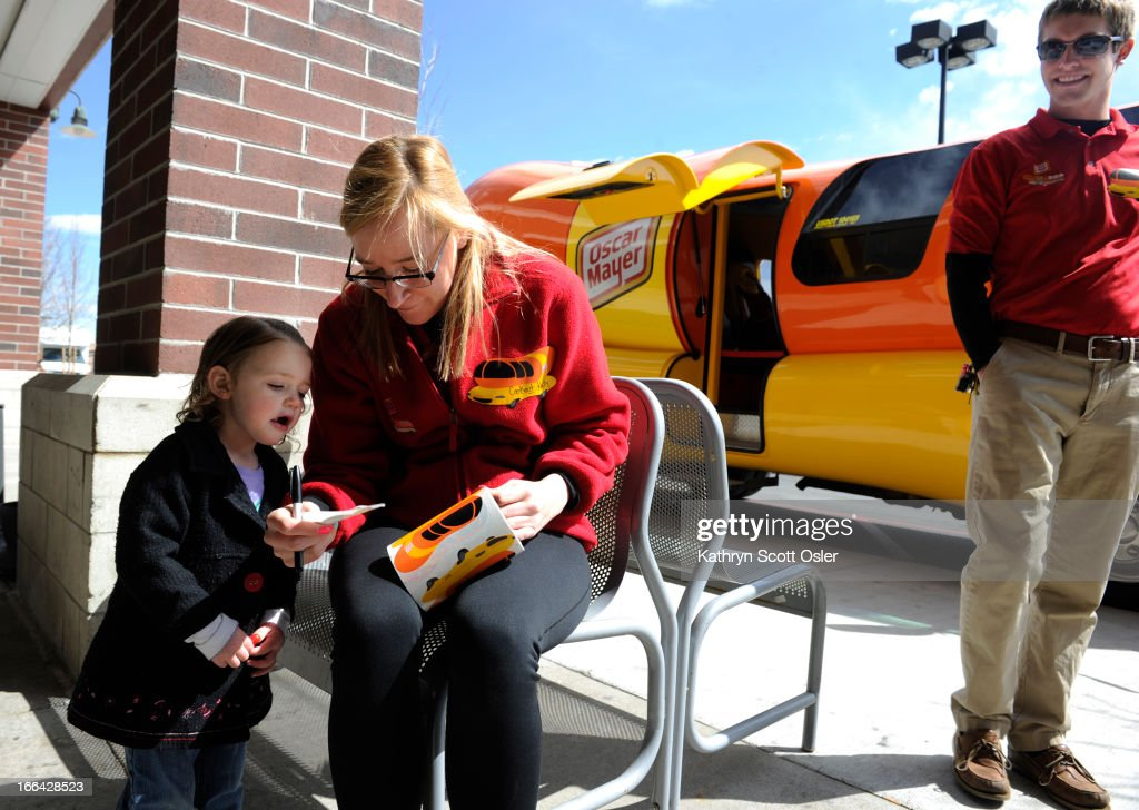The Oscar Mayer Wienermobile rolls through the metro area on its voyage across the country celebrating the 25th anniversary of having the giant hot dog piloted by recent college grads like 'Deli' Eliot Pattee, right, and 'Cookout' Kelly Goldthorpe, giving a sticker to Kenley Taylor, 2. The grads, who are part of the 'hotdogger tradition', must attend two weeks of 'Hotdog High' in Madison Wisconsin and serve as drivers and ambassadors of all things Oscar Mayer for one year. There is still a chance to see the road dog before it hits the highway on its return to Wisconsin from 11 a.m.- 4 p.m Saturday at the Walmart at 440 Wadsworth Blvd. in Lakewood.