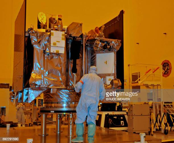 The OSIRISREx spacecraft sits on its workstand August 20 2016 as an engineer examines it in a servicing building at Kennedy Space Center Florida The...