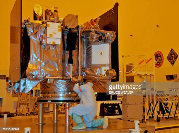 The OSIRISREx spacecraft sits on its workstand August 20 2016 while an engineer checks the protective covering in a servicing building atKennedy...