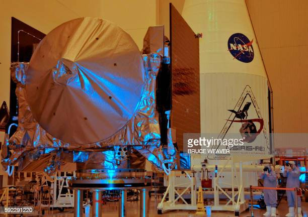 The OSIRISREx spacecraft sits on its workstand August 20 2016 with its launch fairing in a servicing building at Kennedy Space Center Florida The...