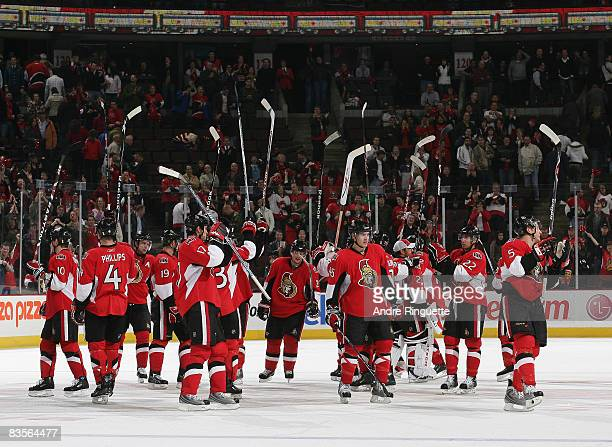 The Ottawa Senators gather at centre ice and raise their sticks to salute the fans after their overtime win against the Washington Capitals on...
