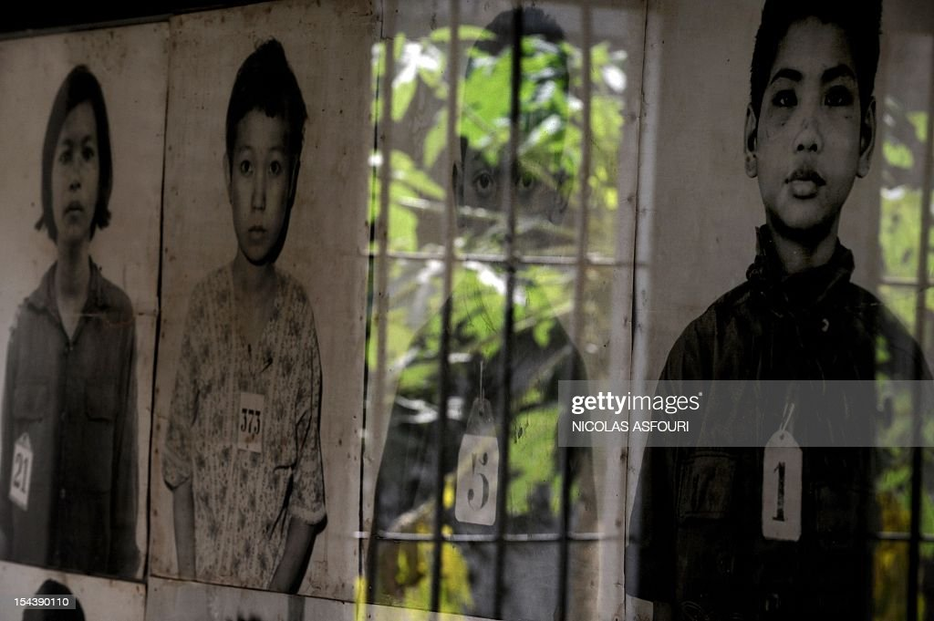 The outside world is reflected in the glass covering a boy's photograph, one of thousands of victims on display at the genocide museum at Tuol Sleng, the former prison S-21 used by the Khmer Rouge to imprison and torture thousands of Cambodians during the 1970s, in Phnom Penh on February 10, 2009. Cambodia's UN-backed genocide tribunal will on February 17, 2009 formally open the long-awaited trial of the Khmer Rouge regime's former Toul Sleng prison chief, Kaing Guek Eav, better known as Duch, who is the first of the five leaders detained by the tribunal. Duch, now 66, faces charges of crimes against humanity, war crimes, torture and pre-meditated murder for his role in running S-21, the Khmer Rouge's notorious main prison, during the 1975-1979 regime. AFP PHOTO / NICOLAS ASFOURI