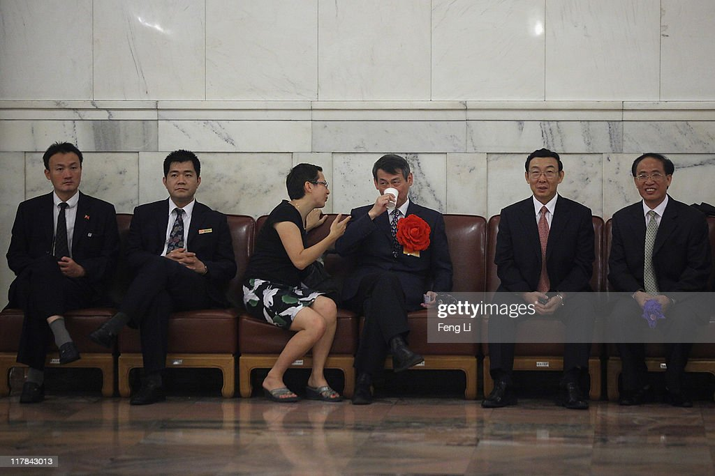 The outstanding members of the Communist Party of China who wears red flower drinks water before the celebration of the Communist Party's 90th anniversary at the Great Hall of the People on July 1, 2011 in Beijing, China.