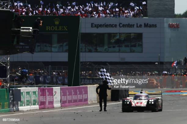 The overall winning The Porsche LMP Team 919 of Earl Bamber Timo Bernhard and Brendon Hartley cross the finish line to win the Le Mans 24 Hours race...