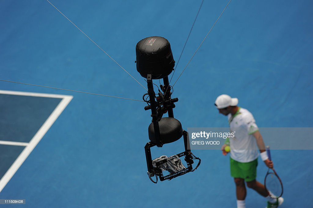 The overhead 'spider cam' camera crosses the court as Jurgen Melzer of Austria prepares to serve against Andy Murray of Britain during their round...
