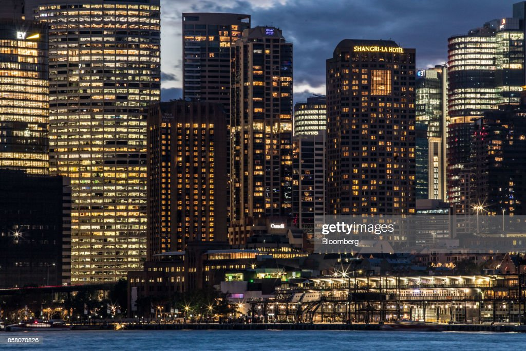 The Overseas Passenger Terminal, foreground right, and buildings in the financial district stand illuminated at dusk in Sydney, Australia, on Friday, Sept. 29, 2017. A bungled transition from coal to clean energy has left resource-rich Australia with an unwanted crown: the highest power prices in the world. Photographer: Cole Bennetts/Bloomberg via Getty Images