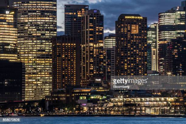 The Overseas Passenger Terminal foreground right and buildings in the financial district stand illuminated at dusk in Sydney Australia on Friday Sept...