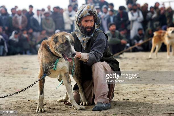 The owner and his dog pause before the start of the dog fights in a slum district of Kabul December 17 2004 in Afghanistan Dog fighting a sport...