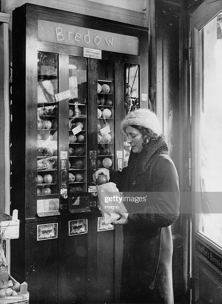 The owner of a fruit store in the Western part of Berlin has put up a vending machine in the shop window from which one can buy fruits of one's own choice. Photograph. Around 1930.
