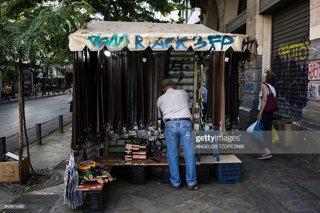 The owner of a kiosk arranges his goods in central Athens on June 25, 2016. / AFP / Angelos Tzortzinis
