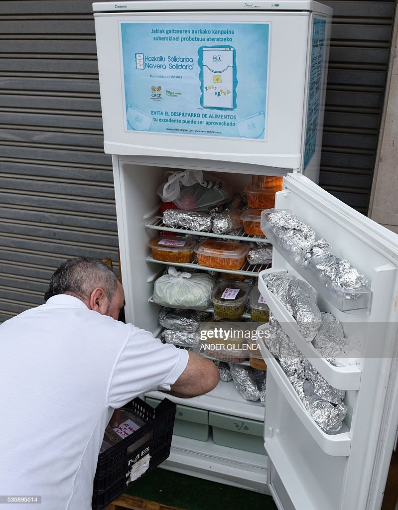 The owner of a restaurant puts food in the 'Solidarity Fridge',a social initiative based on good will with the purpose to help feed the needy and reduce wastage, in the Spanish Basque city of Galdakao on May 30, 2016. The 'refrigerator' project was launched by the Association of Volunteers of Galdakao on 30 April, in a bid to give a second life to leftover food and food about to expire by placing a refrigerator in the street where neighbors and restaurants could deposit their surplus food for people with limited resources to collect and use instead of dumping it. / AFP / ANDER