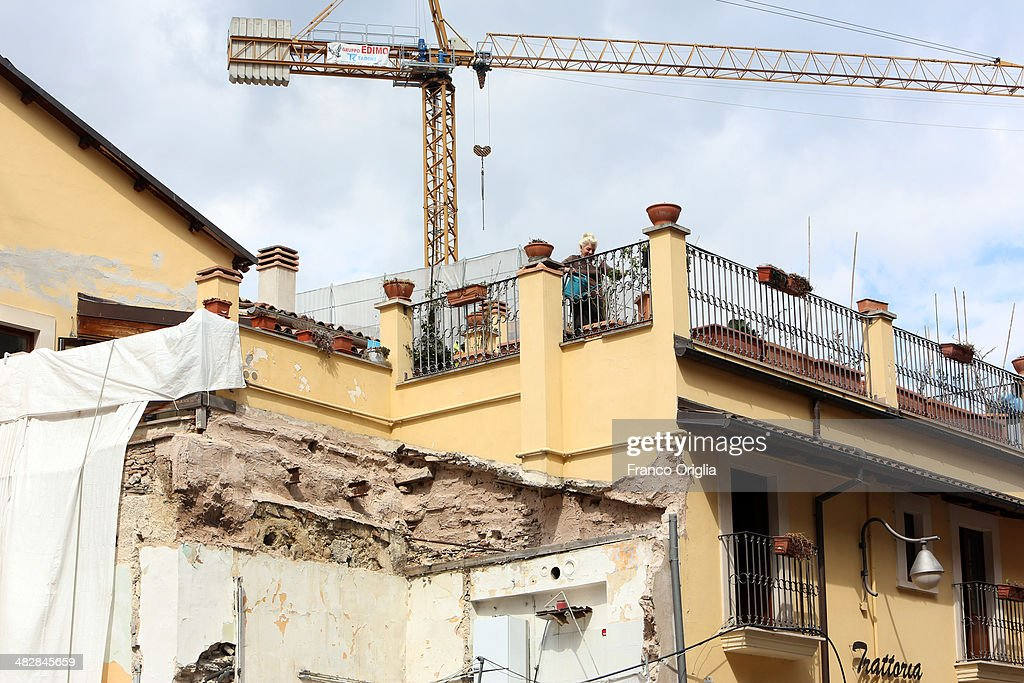 L'AQUILA ITALY MARCH 22 The owner of a traditional restaurant that has just reopened waters her vegetables on a terrace underneath a crane in the...