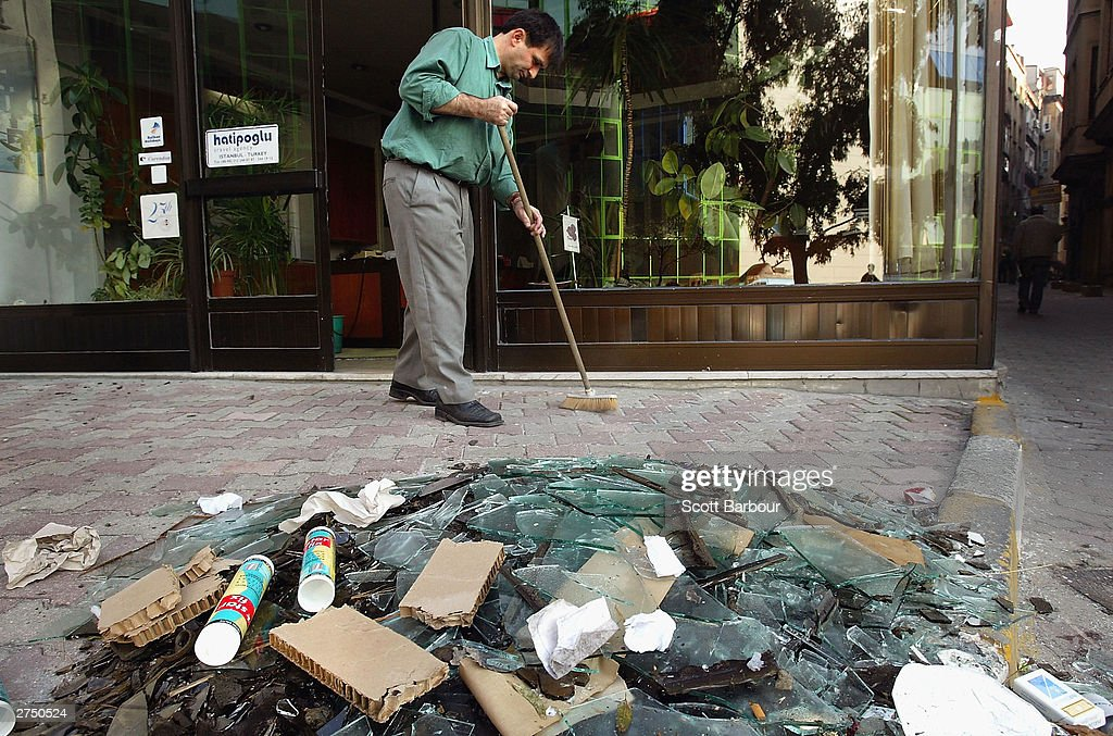 The owner of a Turkish travel agency clears away the rubble from the front of his shop which is located near the scene of the British Consulate bombing November 21, 2003 in Istanbul, Turkey. Bomb attacks on the British consulate and the HSBC bank headquarters on November 20, 2003 killed at least 27 people and left hundreds injured.