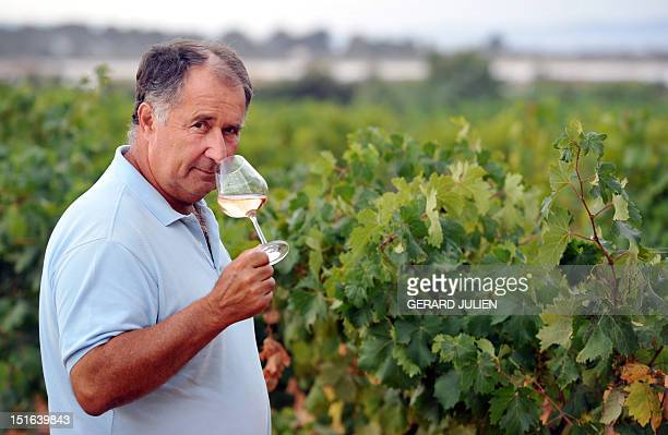 JEANNEAU The owner of the Chateau SainteMarguerite vineyard JeanPierre Fayard poses with a glass of rose wine on August 28 2012 in his domain in La...
