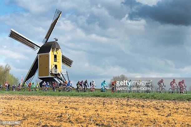 TOPSHOT The pack compete in front of the Hubertus mill on April 17 2016 during the Amstel Gold Race in Beek The Netherlands / AFP / 103266 AND ANP /...