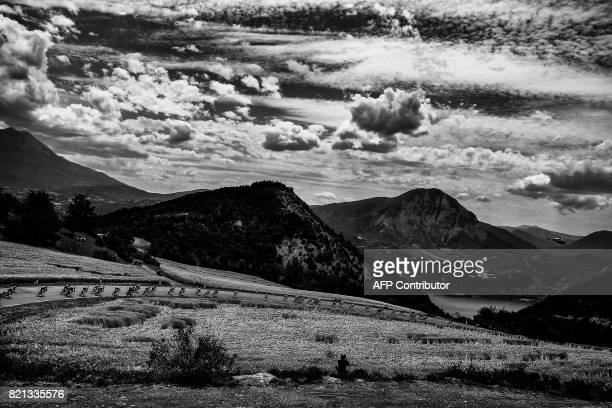 The pack rides during the 2225 km nineteenth stage of the 104th edition of the Tour de France cycling race on July 21 2017 between Embrun and...