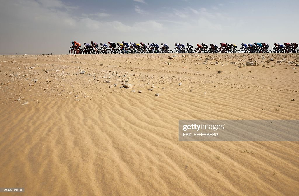 TOPSHOT - The pack rides in the desert during the first stage of the 2016 Tour of Qatar, between Dukhan and Al Khor Corniche on February 8, 2016. Britain's Mark Cavendish, the former world road race champion, took the gold jersey and covered the 175 kilometres from Dukhan to the Al Khor corniche, north of the capital Doha, in 3hrs 28.31secs, eight seconds in front of Modolo and 11 seconds ahead of Guardini. / AFP / ERIC FEFERBERG