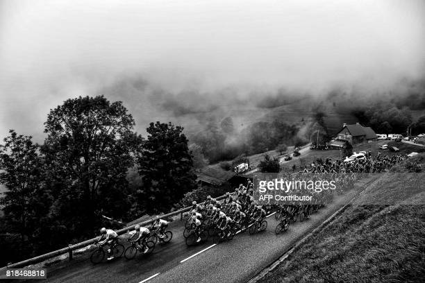 The pack rides in the fog during the 2145 km twelfth stage of the 104th edition of the Tour de France cycling race on July 13 2017 between Pau and...