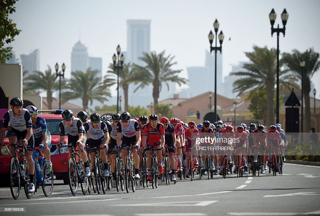 The pack rides in the Pearl Corniche district in Doha during the second stage of the 2016 Tour of Qatar cycling race, starting and finishing at the Qatar University on February 9, 2016. Norway's Alexander Kristoff won a sprint finish ahead of Britain's Marc Cavendish for the second stage of the Tour of Qatar. / AFP / Eric FEFERBERG