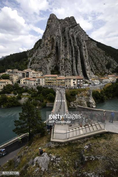The pack rides on a bridge in front of the Rocher de la Baume in Sisteron during the 2225 km nineteenth stage of the 104th edition of the Tour de...