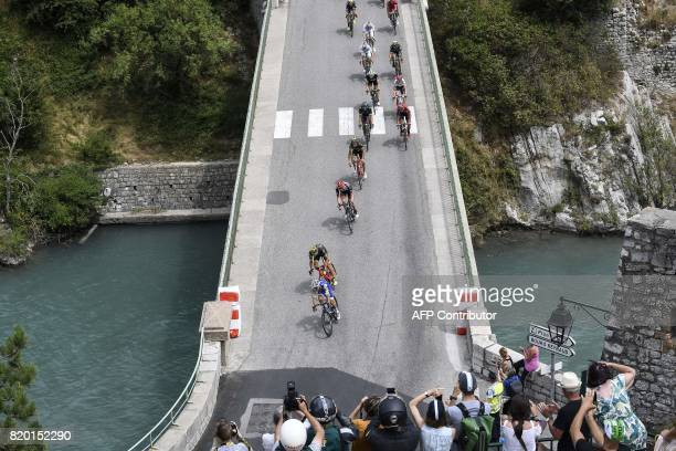 The pack rides on a bridge in Sisteron during the 2225 km nineteenth stage of the 104th edition of the Tour de France cycling race on July 21 2017...
