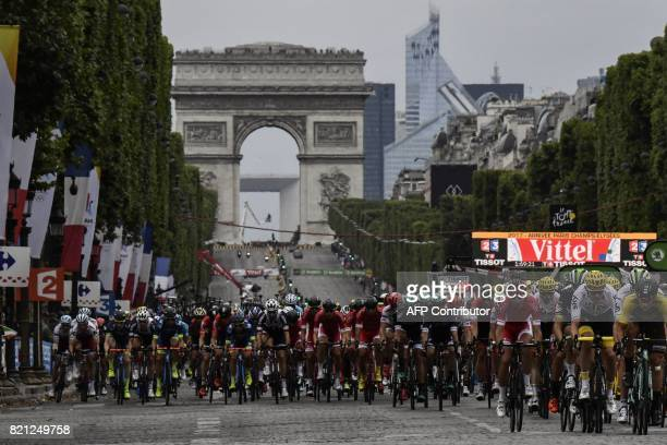 The pack rides on the ChampsElysees avenue with the Arc de Triomphe in the background during the 103 km twentyfirst and last stage of the 104th...