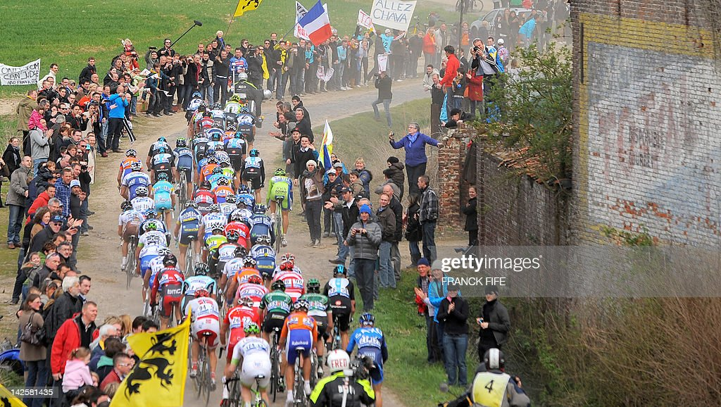 The pack rides on the cobblestoned road during the 110th edition of the Paris-Roubaix cycling race between Compiegne and Roubaix on April 8, 2012, in Roubaix, northern France. Belgian Tom Boonen won the race ahead of French Sebastien Turgot (Team Europcar) and Italian Alessandro Ballan (Team BMC). Bonnen, who had previously won in 2005, 2008 and 2009, equals the record of wins in Paris-Roubaix held by compatriot Roger De Vlaeminck. AFP PHOTO / FRANCK FIFE