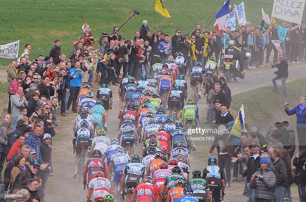 The pack rides on the cobblestoned road during the 110th edition of the Paris-Roubaix cycling race between Compiegne and Roubaix on April 8, 2012, in Roubaix, northern France. Belgian Tom Boonen won the race ahead of French Sebastien Turgot (Team Europcar) and Italian Alessandro Ballan (Team BMC). Bonnen, who had previously won in 2005, 2008 and 2009, equals the record of wins in Paris-Roubaix held by compatriot Roger De Vlaeminck.