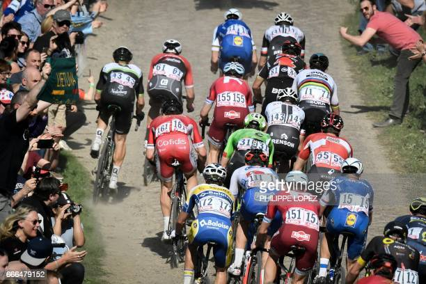 The pack rides on the cobblestones during the 115th edition of the ParisRoubaix oneday classic cycling race between Compiegne and Roubaix on April 9...