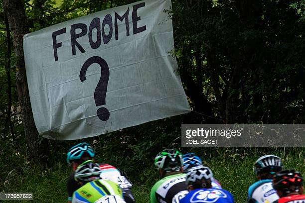 The pack rides past a banner reading 'Froome ' during the 1725 km eighteenth stage of the 100th edition of the Tour de France cycling race on July 18...