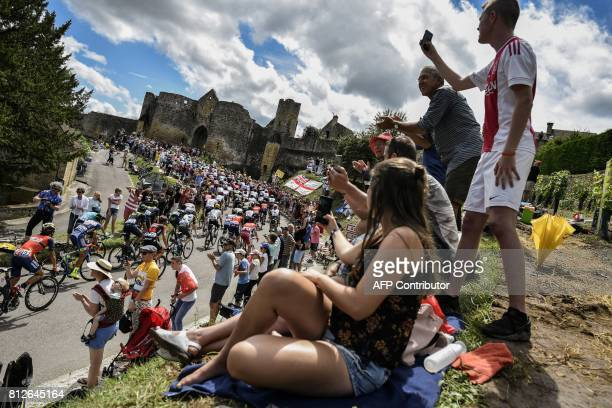 TOPSHOT The pack rides past a castle as fans cheer during the 178 km tenth stage of the 104th edition of the Tour de France cycling race on July 11...