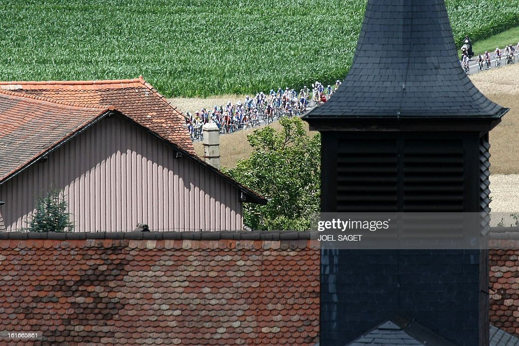 The pack rides past a church on July 19, 2009 in the 207,5 km and fifteenth stage of the 2009 Tour de France cycling race run between Pontarlier and Verbier (Switzerland). AFP PHOTO JOEL SAGET