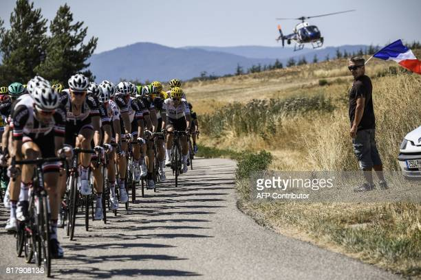 TOPSHOT The pack rides past a supporter holding up a French flag as a media helicopter flies beside during the 165 km sixteenth stage of the 104th...
