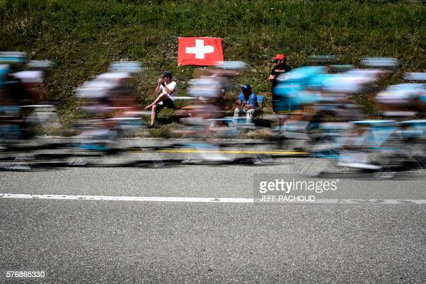TOPSHOT The pack rides past Swiss fans next to a Switzerland's national flag during the 209 km sixteenth stage of the 103rd edition of the Tour de...