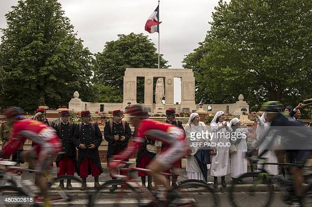 The pack rides past the Albert's World War I memorial in Albert as supporters dressed as WWI soldiers or nurses cheer during the 1895 km fifth stage...