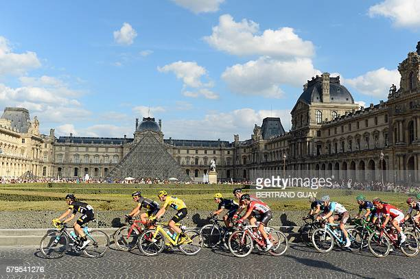 The pack rides past the Pyramide du Louvre during the 113 km twentyfirst and last stage of the 103rd edition of the Tour de France cycling race on...