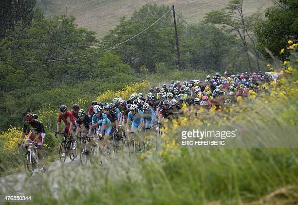 The pack rides under heavy rain during the 228 km fourth stage of the 67th edition of the Dauphine Criterium cycling race on June 10 2015 between...