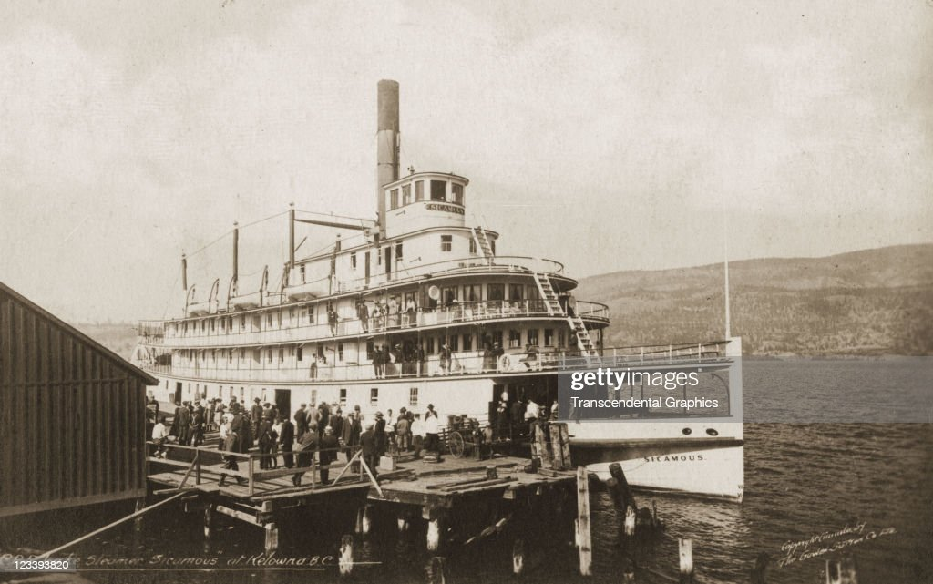 The paddle wheeler Sicamous docks and discharges passengers in this photographic postcard made early 20th century in Kelowna British Columbia Canada