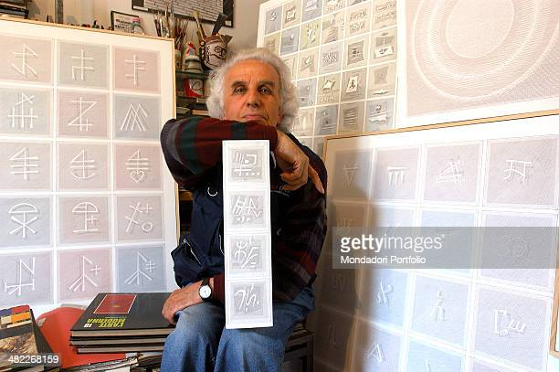 The painter Giovanni La Rosa native of Varese sits in his study surrounded by some of his works bsed on the alphabet a beloved theme ideograms...