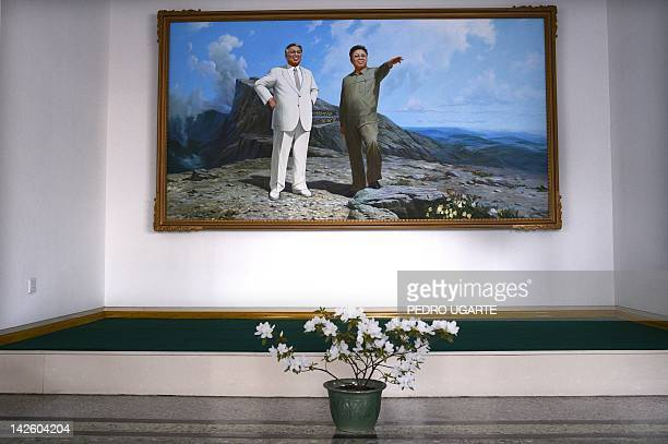The painting of North Korea's late presidents Kim IlSung and his son Kim JongIl hang in an auditorium of a textile factory in Pyongyang on April 9...