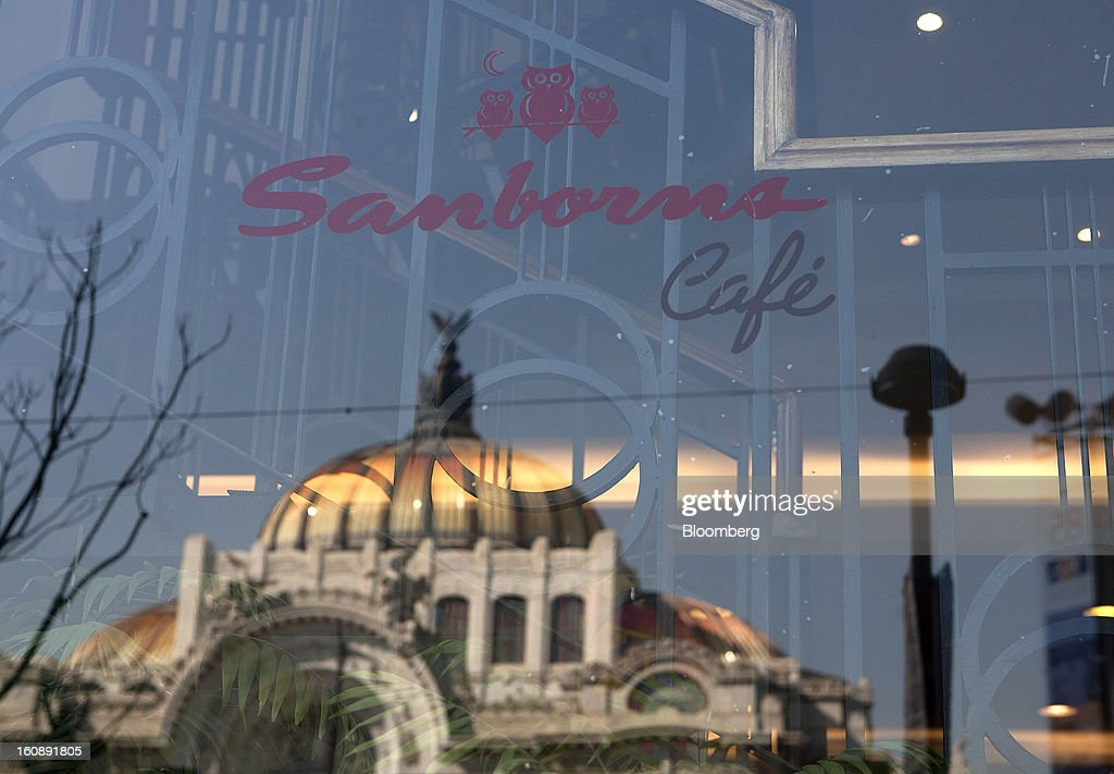 The Palacio de Bellas Artes is reflected in the window of a Sanborns Grupo SAB cafe on Juarez Avenue in Mexico City, Mexico, on Thursday, Feb. 7, 2013. Billionaire Carlos Slim is taking Mexican retailer Grupo Sanborns SAB public as revenue surges from sales to consumers looking to shop at its Saks Fifth Avenue stores and buy Apple Inc. iPads. Photographer: Susana Gonzalez/Bloomberg via Getty Images