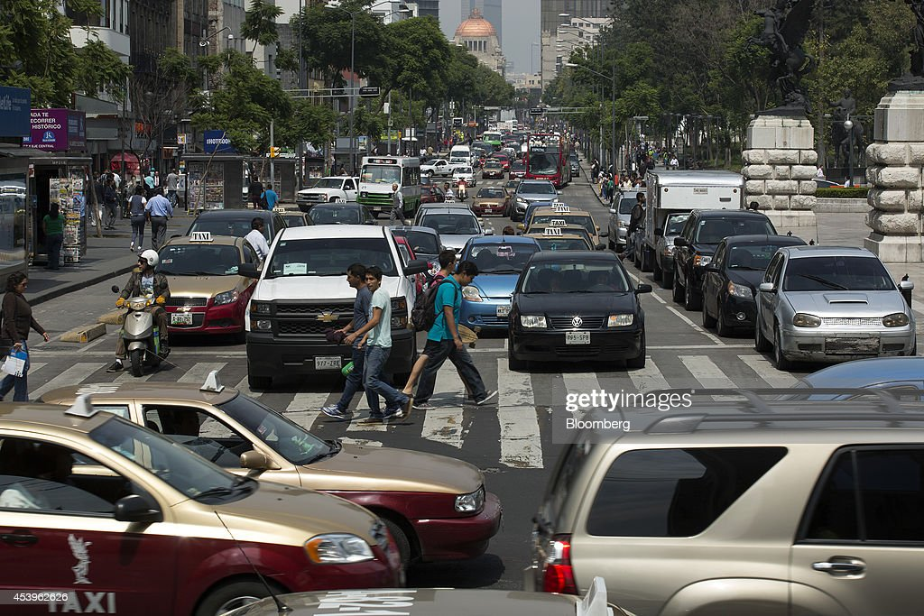 The Palacio de Bellas Artes stands in the background as pedestrians cross the street in downtown Mexico City, Mexico, on Thursday, Aug. 21, 2014. Mexican consumer prices rose more than analysts expected in the first half of August and the unemployment rate rose to 5.47 percent in July compared with 4.8 percent in June. Photographer: Susana Gonzalez/Bloomberg via Getty Images