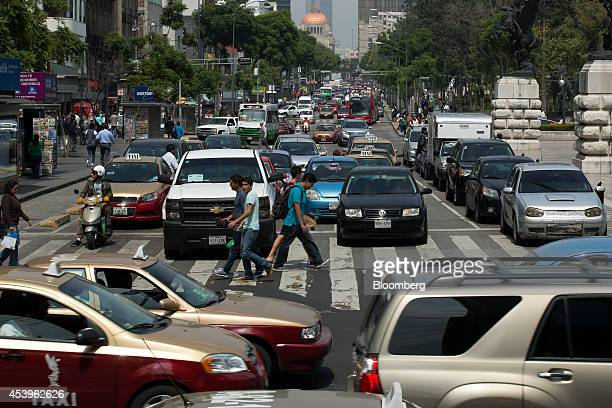 The Palacio de Bellas Artes stands in the background as pedestrians cross the street in downtown Mexico City Mexico on Thursday Aug 21 2014 Mexican...