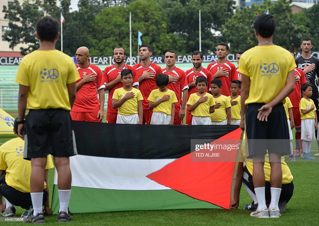 The Palestinian football team listen to their anthem next to their flag prior to their knockout game of the Peace Cup invitational tournament in...