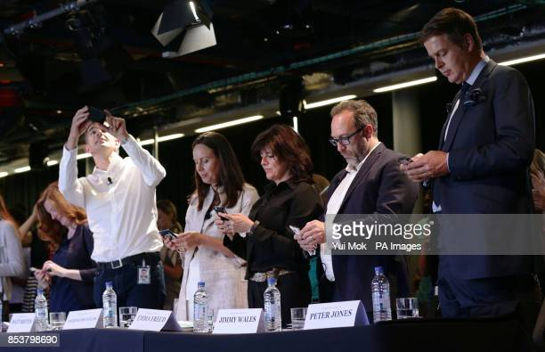 The panel of judges Helen Goulden Matt Brittin Jacquelline Fuller Emma Freud Jimmy Wales and Peter Jones CBE tweeting on their phones during the...