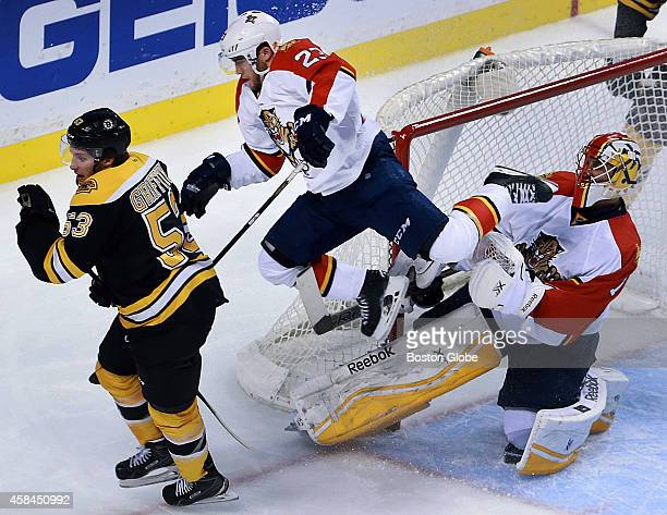The Panthers Rocco Grimaldi sails by his goalie Roberto Luongo as he and the Bruins Seth Griffith pursue a second period puck The Boston Bruins...