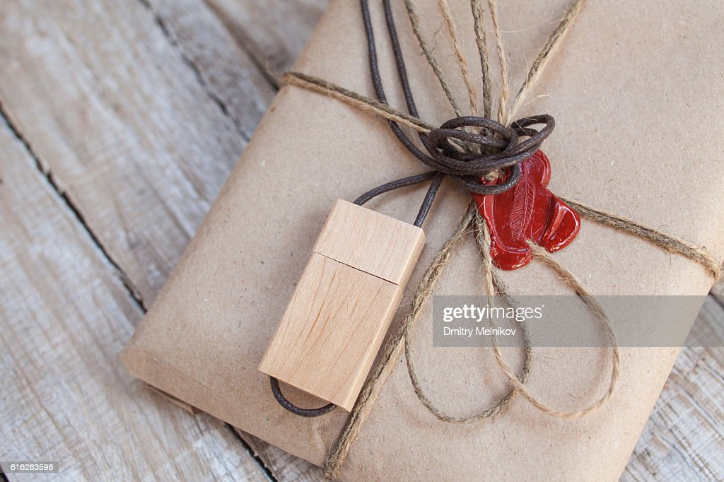 The parcel wrapped in Kraft on a wooden background. : Stock Photo