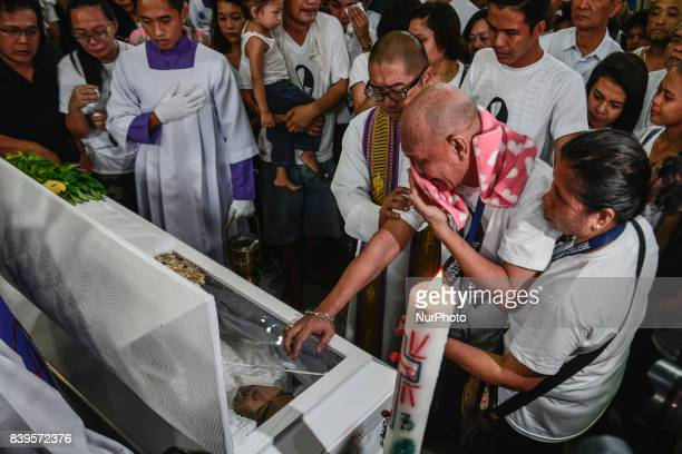 The parents and relatives of Kian Loyd Delos Santos weep over his coffin during his funeral rites in Caloocan Metro Manila Philippines August 26 2017...